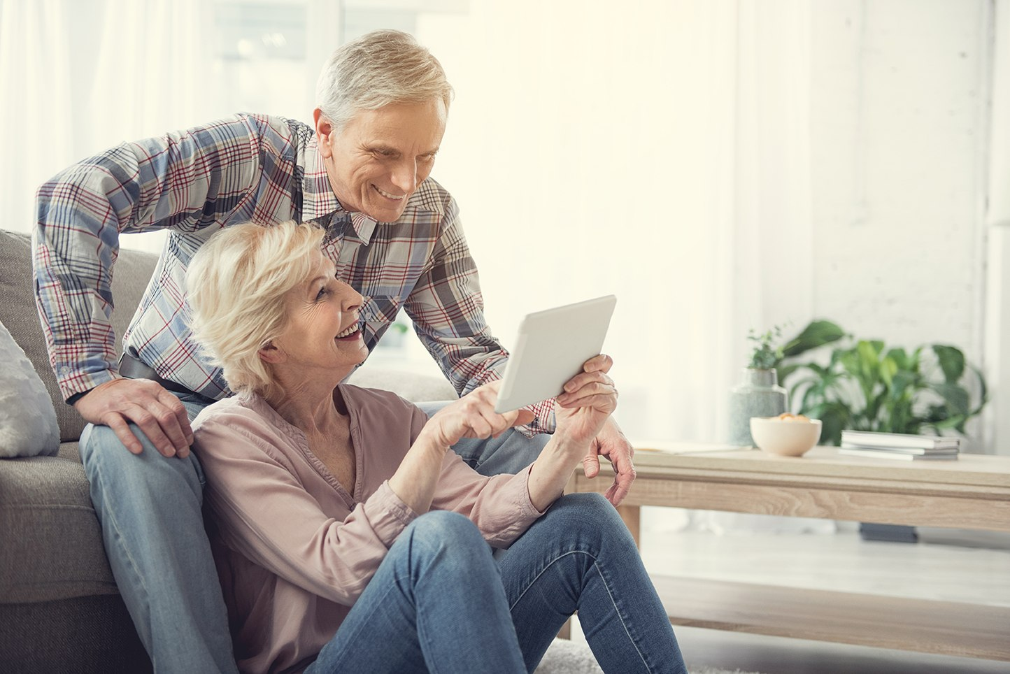 Elderly couple looking at a tablet smiling